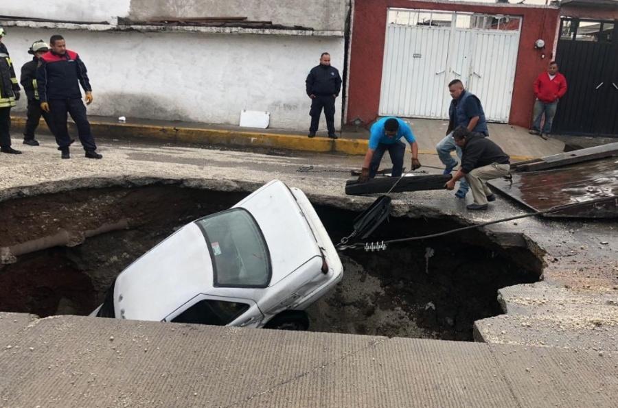 Caen dos vehículos en enorme socavón en Ecatepec