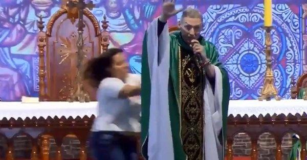Mujer empuja a un sacerdote durante una ceremonia