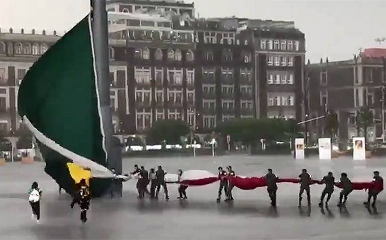 Ciudadanos auxilian a militares al bajar bandera monumental