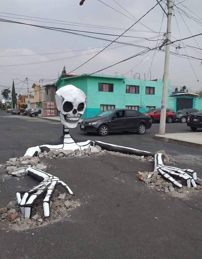 """Con calaveras gigantes, vecinos """"tapan"""" baches en Tláhuac"""