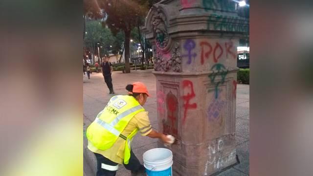 Mujeres limpian pintas tras la marcha de ayer