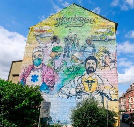 Artistas callejeros pintan mural en Bruselas en honor al personal que combate el Covid-19