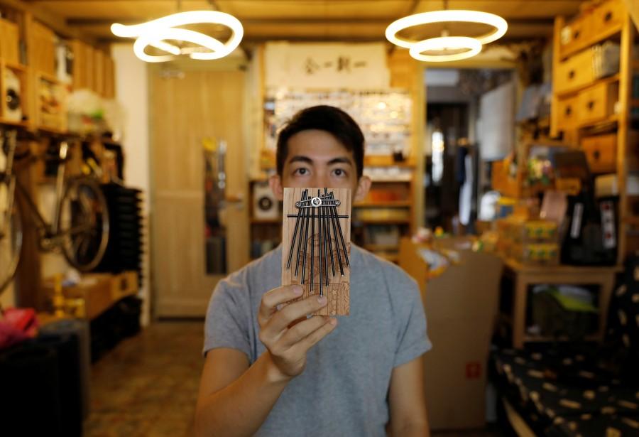 Con paraguas, Kevin Cheung elabora pianos de pulgar
